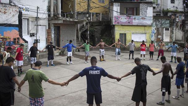 Friends and neighbours of the late Douglas Rafael da Silva Pereira pray near the spot where his body was found (AP)