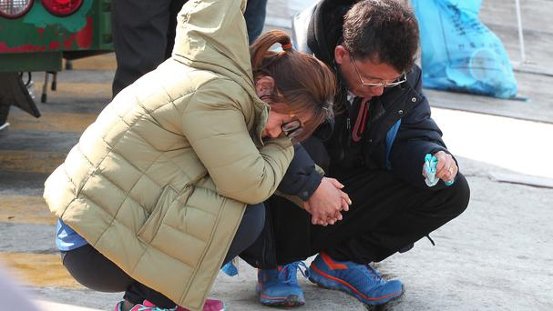 Relatives of a passenger aboard the sunken ferry Sewol weep as they wait for news of their missing loved one at a port in Jindo (AP)