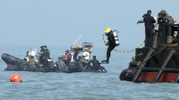 A diver jumps into the sea to look for people believed to have been trapped in the sunken Sewol ferry (AP)