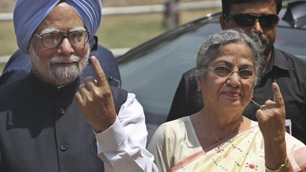 PM Manmohan Singh and his wife Gursharan Kaur show the ink mark on their index fingers after casting their vote during the sixth phase of polling of the Indian parliamentary elections in Gauhati (AP)
