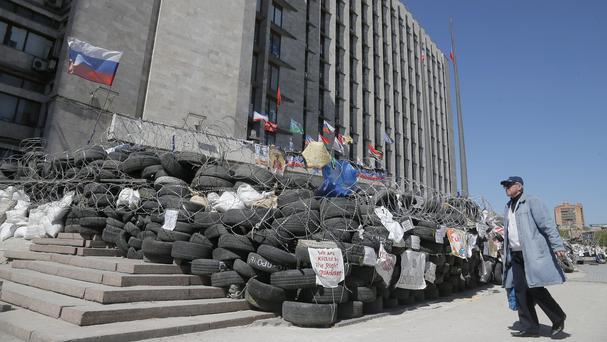 A man walks near a barricade at the regional administration building in Donetsk, Ukraine (AP)