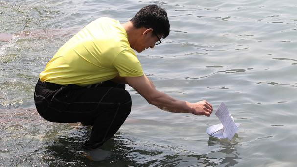 A relative of a passenger aboard the sunken ferry Sewol releases a paper boat with messages to wish for the safe return of his missing loved one at a port in Jindo (AP)