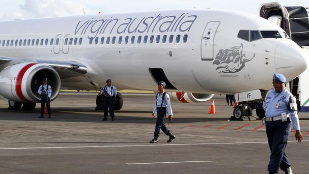 Indonesian air force personnel stand guard near a Virgin Australia plane in Bali (AP)