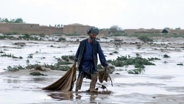 An Afghan man carries his belongings over wet ground after a flood in Jawzjan province (AP Photo/Mustafa Najafizada)