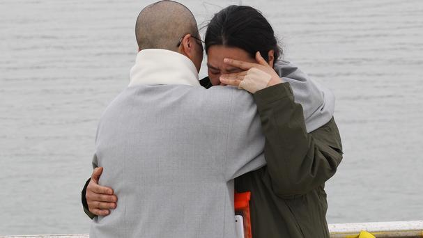 A relative of a passenger aboard the sunken ferry Sewol is consoled by a Buddhist nun as she waits for news of her missing loved one at a port in Jindo, South Korea (AP)