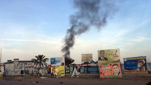 Smoke rises after a series of bombs exploded at a campaign rally for a Shiite group in Baghdad (AP)