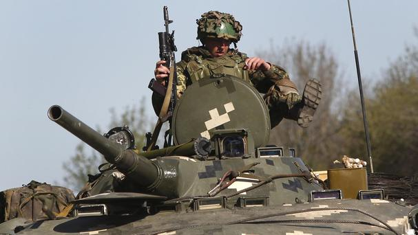 A Ukrainian government soldier sits atop an armoured personnel carrier guarding a checkpoint near the village of Dolina, 18 miles from Slovyansk (AP)