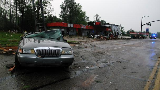 A car with its windows smashed and top caved in sits in front of a petrol station that was heavily damaged by a tornado in Tupelo, Mississippi (AP)