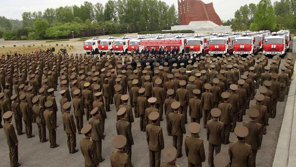 North Korean military stand facing a row of new fire engines, donated to Pyongyang by the Russian government (AP)