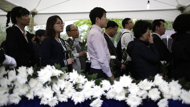 Mourners wait to pay tribute to the victims of the sunken ferry at a group memorial altar in Seoul (AP)