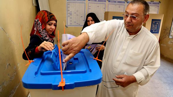 An Iraqi man casts his vote inside a Baghdad polling station during parliamentary elections