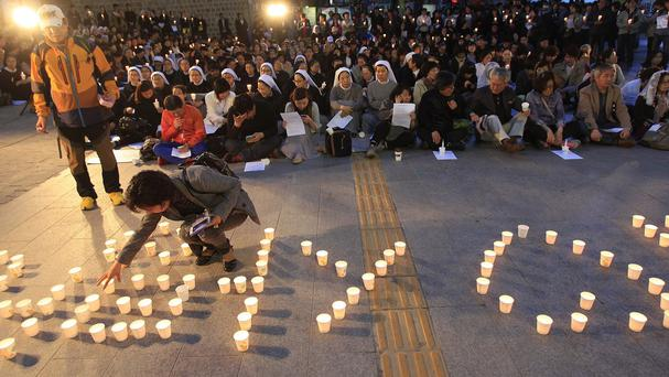 A woman places a candle to form the word 'love' during a service paying tribute to the victims of the sunken ferry Sewol in Seoul, South Korea (AP)