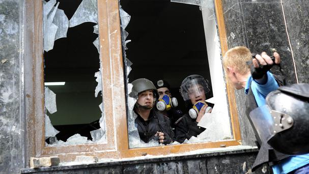 A pro-Russian activist, right, speaks with police officers during clashes in front of the regional administration building in Donetsk, Ukraine (AP)