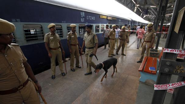 Indian policemen stand guard next to a passenger train that was ripped by two blasts at the railway station in Chennai (AP)