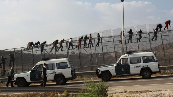 Guardia Civil officers cordon off the area as sub-Saharan migrants stand on top of a fence that divides Morocco and the Spanish enclave of Melilla (AP)