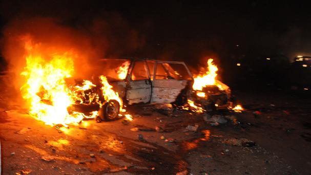 A vehicle burns after a car bomb exploded in Nigeria's capital Abuja (AP)