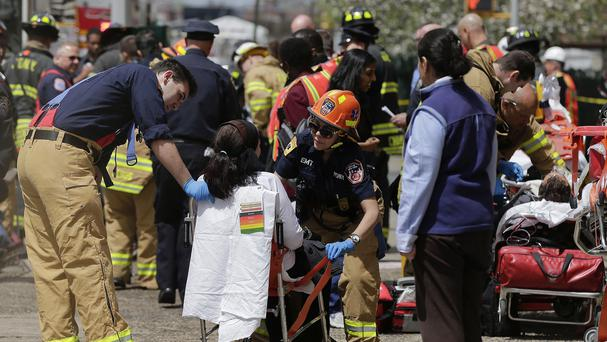 Emergency crews assist a woman who was evacuated from a subway train after it derailed in the Queens borough of New York (AP)