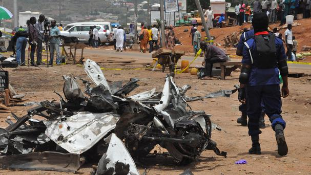 People walk past a damaged car following a bomb explosion in Abuja on Friday