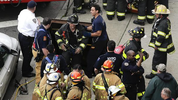 Firefighters emerge from a hatch in the pavement after evacuating passengers from a subway train that derailed in New York (AP)