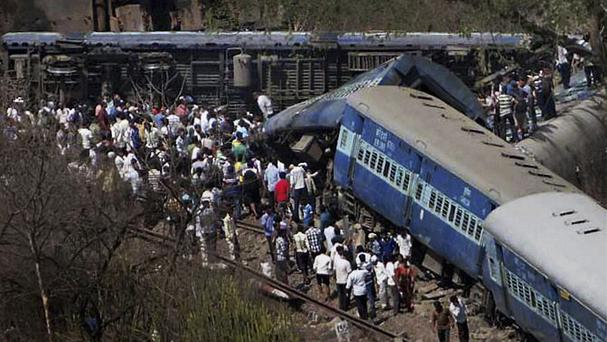People gather around a passenger train that derailed near Roha station, 70 miles south of Mumbai (AP)