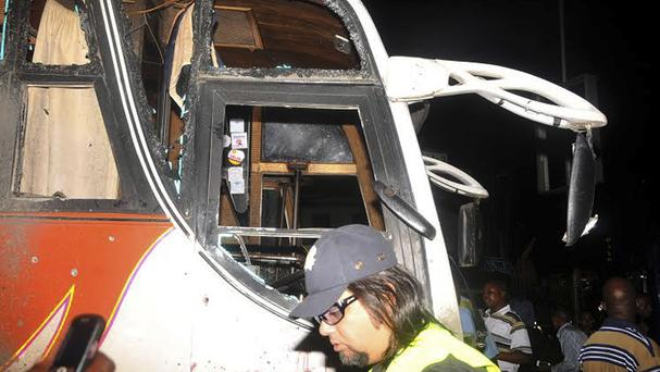 People stand near to a bus with windows shattered after an explosion in Mombasa (AP Photo)