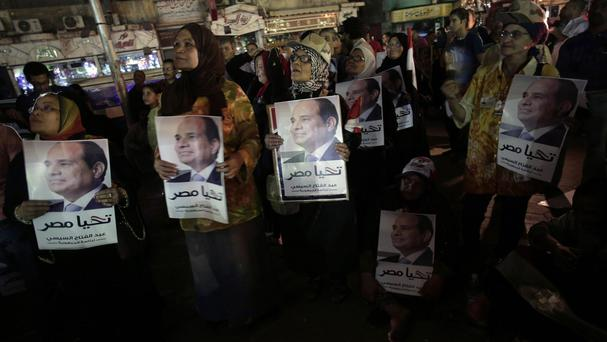 Supporters of Egypt's former army chief Abdel-Fattah el-Sissi hold posters of him with Arabic writing that reads,