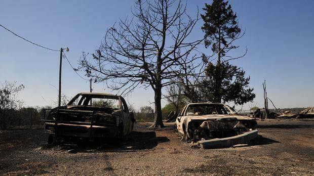 The charred remains of two cars in Guthrie, Oklahoma, the day after a wildfire tore through the area (AP)