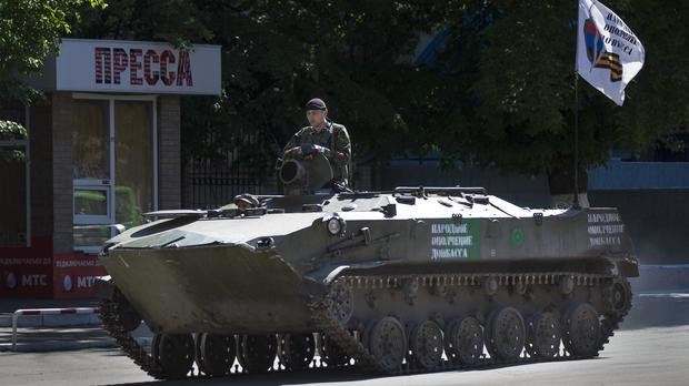 A pro-Russian militant sits on an armoured personal carrier with a Donetsk republic flag rolling through a street in Slovyansk, Ukraine (AP)