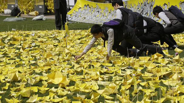 Students put paper ships to pay tribute to the victims and missing passengers of the sunken ferry Sewol at a group memorial altar in Seoul, South Korea (AP)