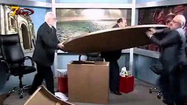 The on-air fight between Jordanian journalists Mohammad al-Jayousi, left, and Shaker al-Johari, right, during a talk show over a disagreement on the Syrian crisis.