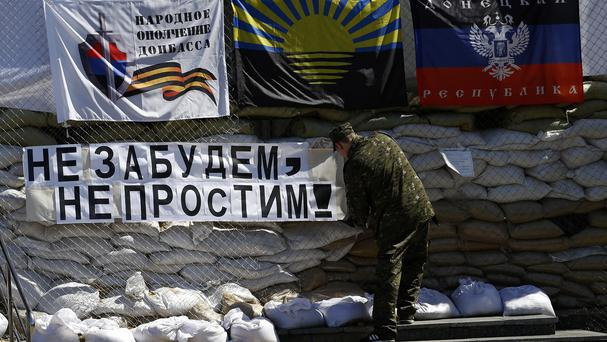 A pro-Russian gunman hangs a banner that reads: