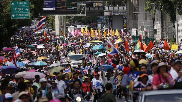 Anti-government protesters march through a main road in downtown Bangkok (AP)