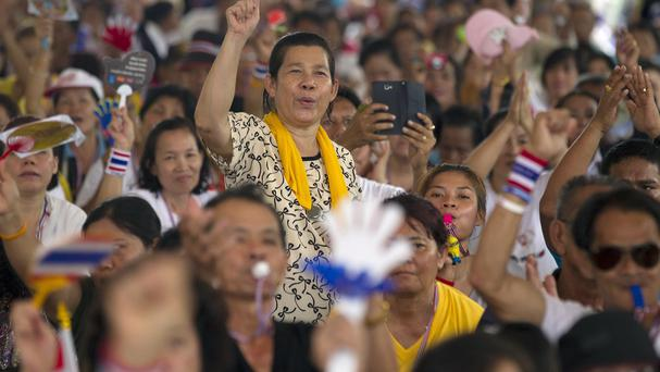 An anti-government protester raises her arm as she listens to a speech delivered by their leader Suthep Thaugsuban during a rally in Bangkok (AP)