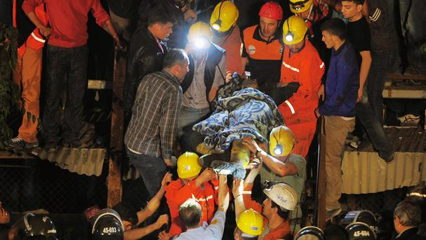 Miners carry a rescued colleague after an explosion and fire at a coal mine killed 200 workers and left dozens trapped underground in Soma, western Turkey (AP)