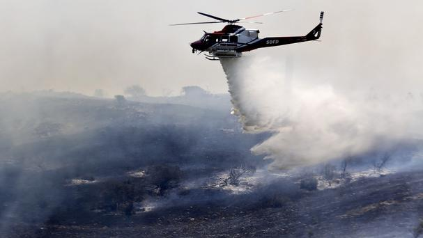 A helicopter attacks a wildfire burning near San Diego (AP)