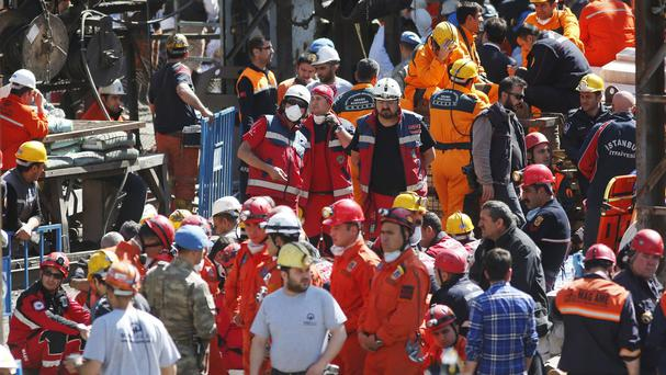Miners and members of the rescue services wait outside a coal mine in Soma, western Turkey (AP)