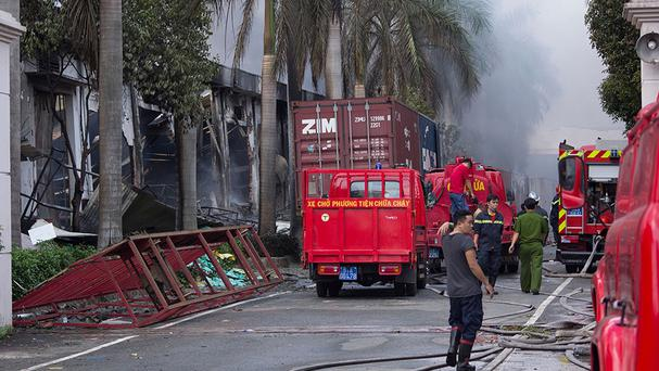 Firefighters at the main entrance of Tan Than Industries as the Taiwanese bicycle factory burns (AP)