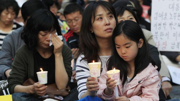 A mother and her daughter hold candles during a rally to pay tribute to the victims of the sunken ferry Sewol (AP)
