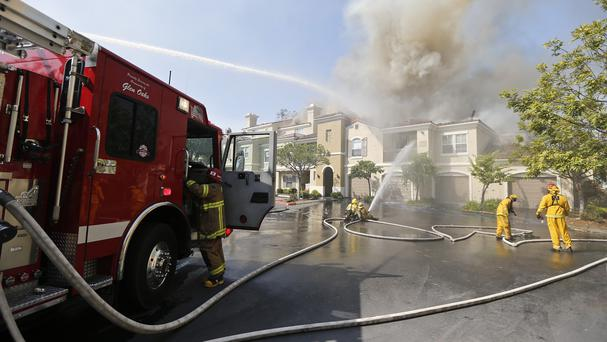Firefighters pour water on homes that were caught in the path of a wildfire in Carlsbad, California (AP)