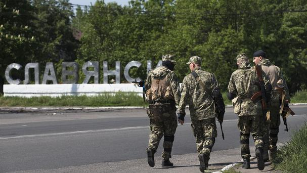 Pro-Russian gunmen walk past a checkpoint blocking the major highway outside Slovyansk, eastern Ukraine (AP)