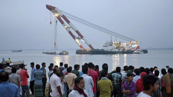 Relatives of passengers aboard the sunken ferry watch a rescue operation on the banks of the River Meghna (AP)