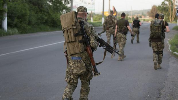 Pro-Russian militants walk to their positions to fight against Ukrainian government troops (AP)