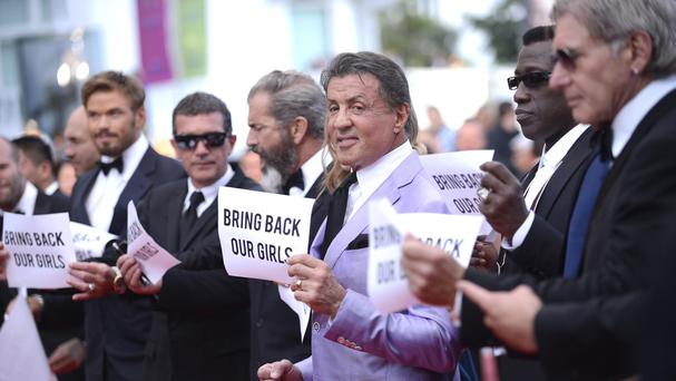 Actor Sylvester Stallone, centre, stands with the cast of The Expendables 3, holding up banners in support of the kidnapped Nigerian schoolgirls
