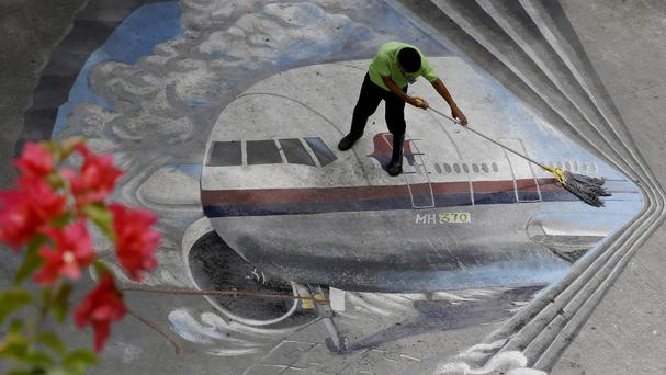 A school worker cleans a mural depicting the missing Malaysia Airlines Flight 370 at the Benigno 'Ninoy' Aquino High School at Makati city east of Manila, Philippines (AP)