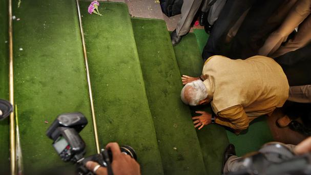India's next prime minister Narendra Modi kisses the steps of the Indian parliament as he arrives for the BJP parliamentary party meeting (AP)