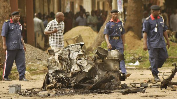 Security forces walk past the remains of a car used in a bombing in Nigeria (AP)