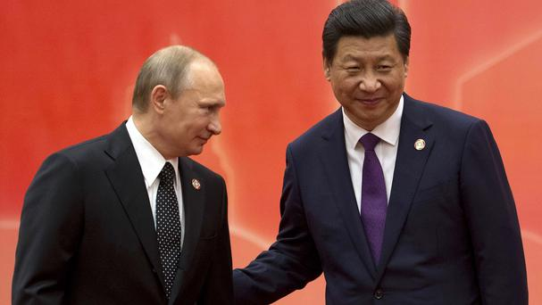 Russian president Vladimir Putin is greeted by Chinese president Xi Jinping (AP)
