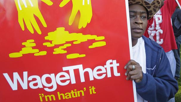 A young man holds a sign as hundreds of workers and supporters gather outside McDonald's in Illinois for a protest last year (AP)