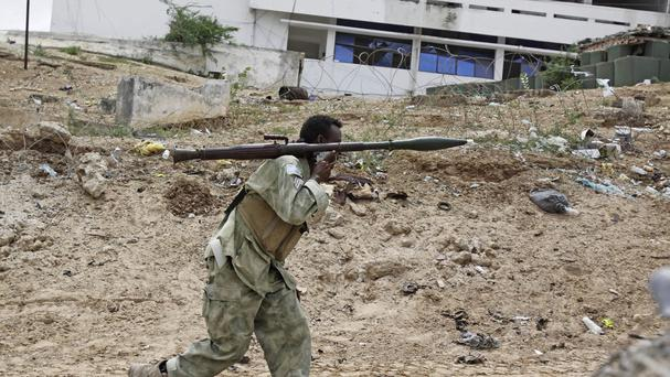 A Somali soldier carrying a rocket launcher runs to fight during an attack on Somalia's parliament in Mogadishu. (AP)