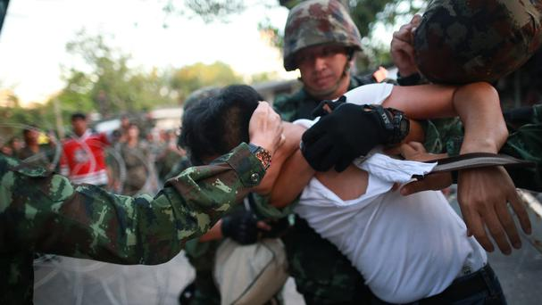 A protester is detained by Thai soldiers during an anti-coup demonstration at the Victory Monument in Bangkok (AP)